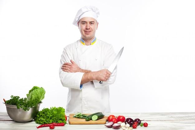 Cuoco unico che posa con il coltello nella sua cucina Foto Gratuite