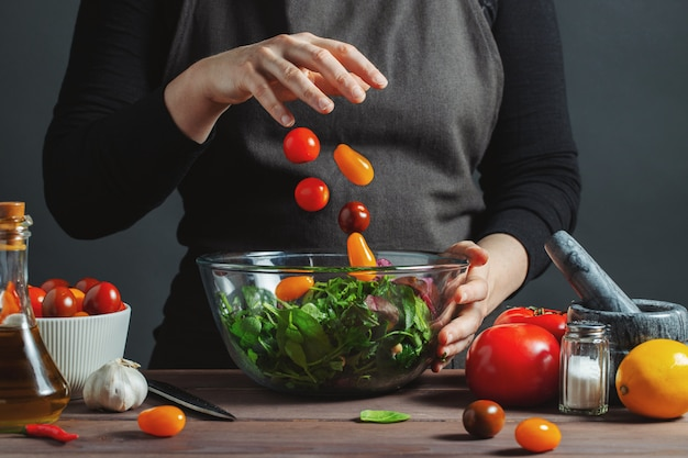Chef pours cherry tomatoes in a bowl Premium Photo