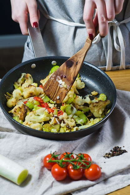 The chef prepares cauliflower and leek in a frying pan. Premium Photo