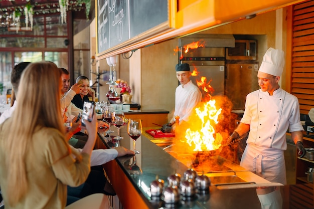 The chef prepares food in front of the visitors in the restaurant Premium Photo
