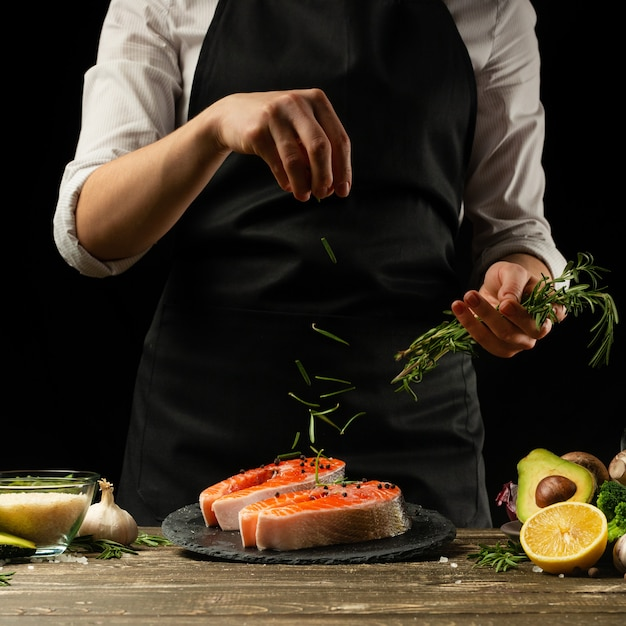 The chef prepares fresh salmon fish, freshly salted trout, sprinkled with rosemary leaves with ingredients. Premium Photo