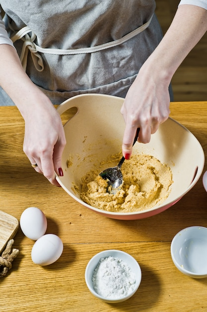 The chef prepares oatmeal cookies, mixes cane sugar and butter. ingredients oat flakes, butter, sugar, eggs, chocolate. Premium Photo