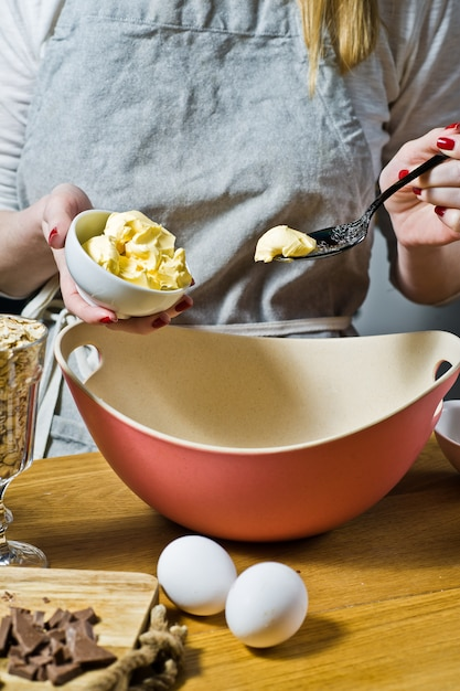 The chef prepares oatmeal cookies, puts butter in a bowl. ingredients oat flakes, butter, sugar, eggs, chocolate. Premium Photo