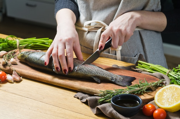 The chef prepares raw trout on a wooden chopping board. Premium Photo