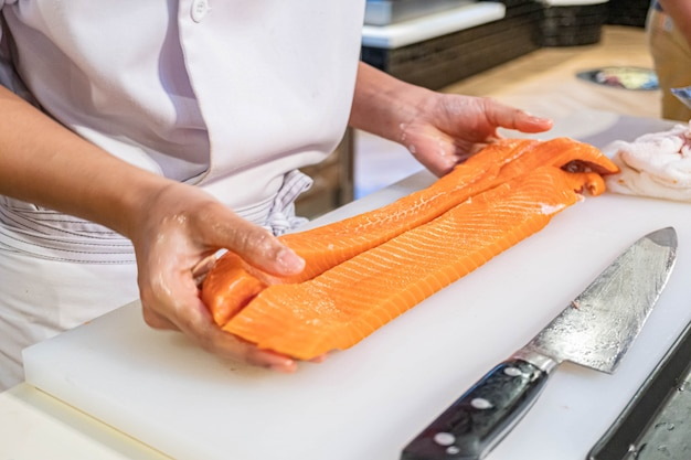Chef preparing and cutting  fresh salmon in japanese restaurant Premium Photo