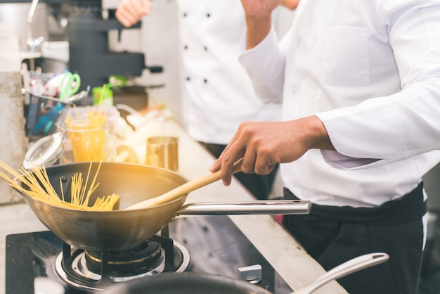 Chef preparare il cibo in cucina di un ristorante Foto Gratuite