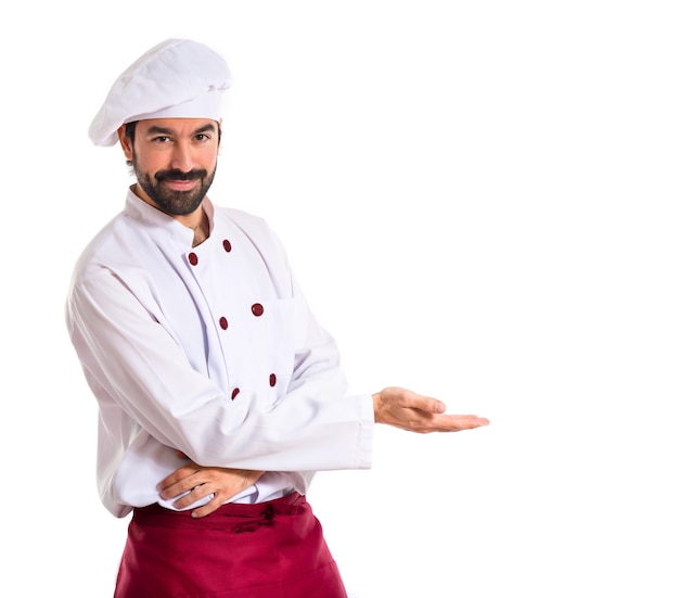 Chef presenting something over white background Free Photo