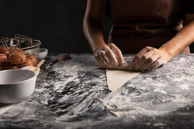 Cuoco unico che rotola il triangolo della pasta per croissant Foto Gratuite