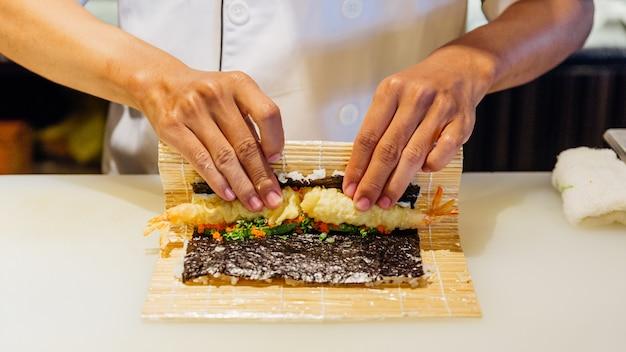 Шеф-повар катит маки-суши с рисом, креветкой-темпурой, авокадо и сыром внутри покрытой хрустящей мукой из темпуры. Premium Фотографии