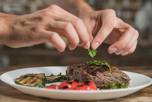 A chef's hand garnishing coriander on roasted beef Free Photo
