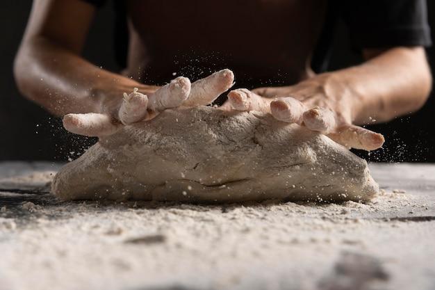 Mani dello chef che impastano la pasta con la farina Foto Gratuite