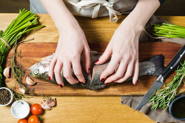 The chef salts raw trout on a wooden chopping board. ingredients rosemary, lemon, tomatoes, garlic, salt, pepper. Premium Photo