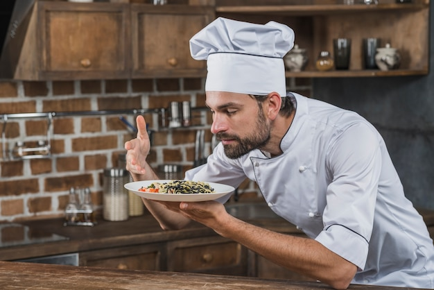 Chef smelling the aroma of dish in the kitchen Free Photo
