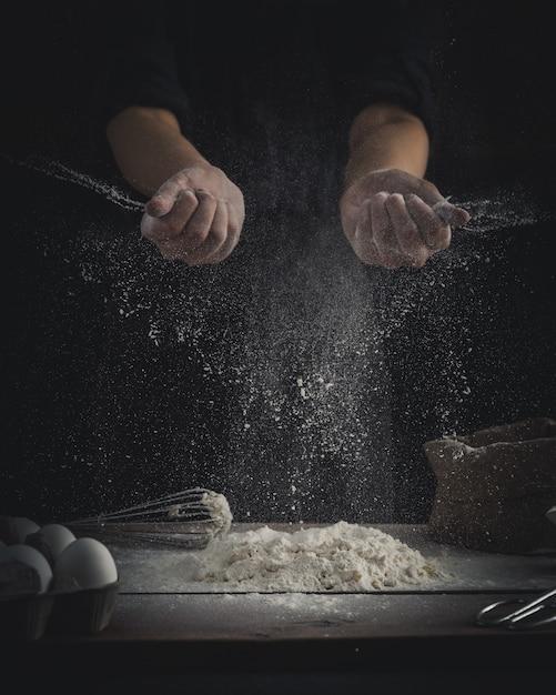 Chef sprinkling flour Free Photo