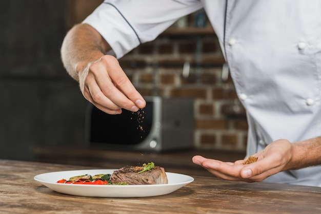 Chef sprinkling spices over the prepared dish Free Photo