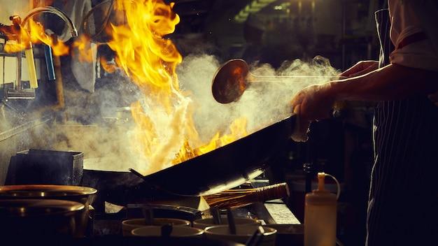 Chef stir fry in wok Premium Photo