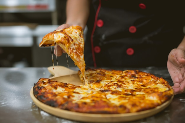 Chef taking pizza at kitchen Free Photo
