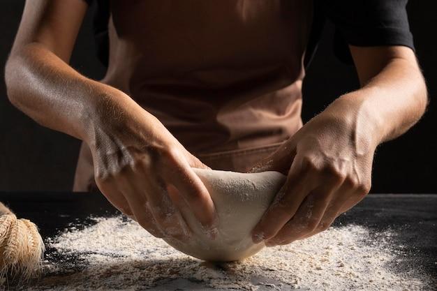 Chef usa la farina per impastare l'impasto in modo che non si attacchi alle mani Foto Gratuite