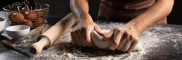 Chef usando le mani e la farina per impastare la pasta Foto Gratuite