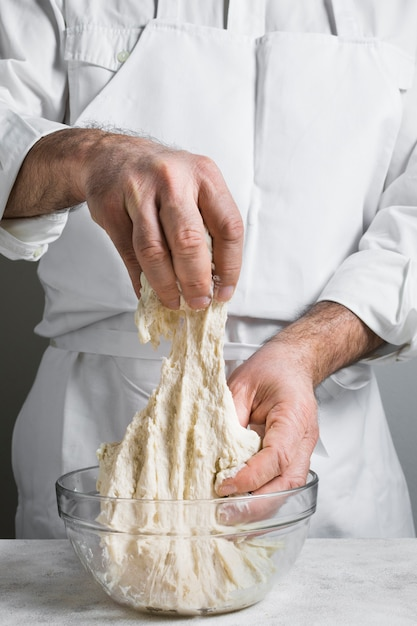 Chef in white clothes making dough Free Photo