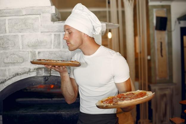 Chef in a white uniform prepare a pizzaa Free Photo