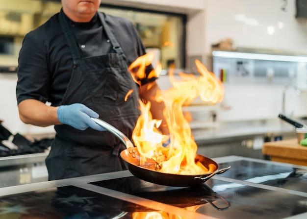 エプロンと手袋のフランベ料理を持つシェフ Premium写真