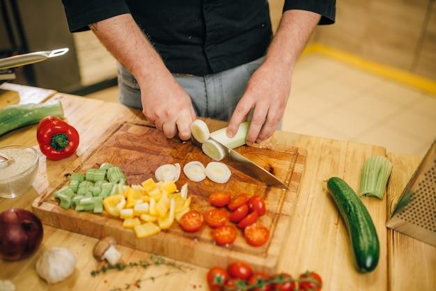 ナイフでシェフが木の板にキノコをカットします。 Premium写真