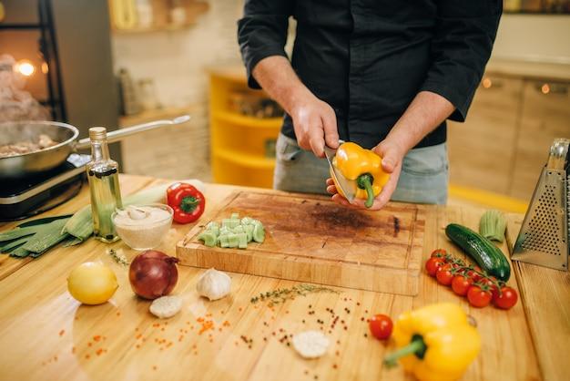 ナイフでシェフが木の板に黄色の唐辛子をカットします。 Premium写真