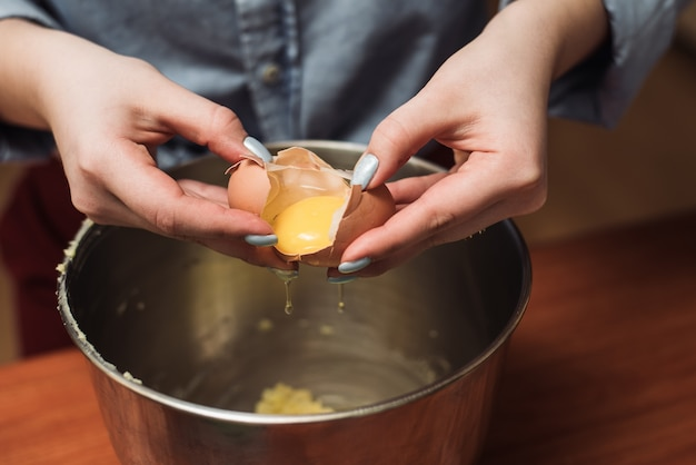 Chef woman breaks eggs in a bowl for dough. adding egg yolk to cooking. the man breaks the egg into a metal bowl Premium Photo