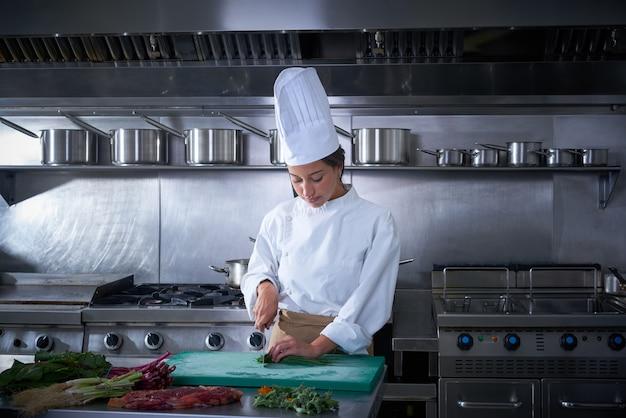 Chef woman portrait cutting at kitchen Premium Photo