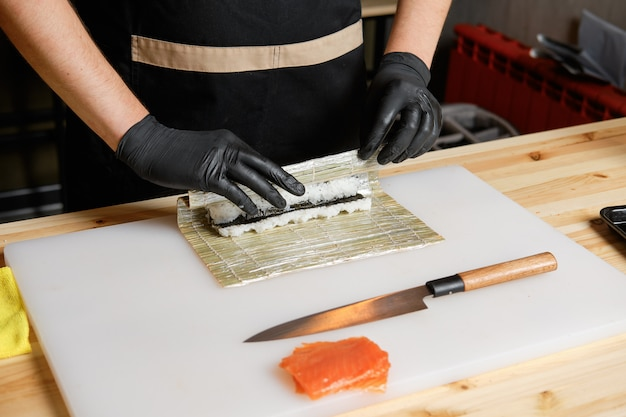 Chef wrapping salmon rolls Premium Photo