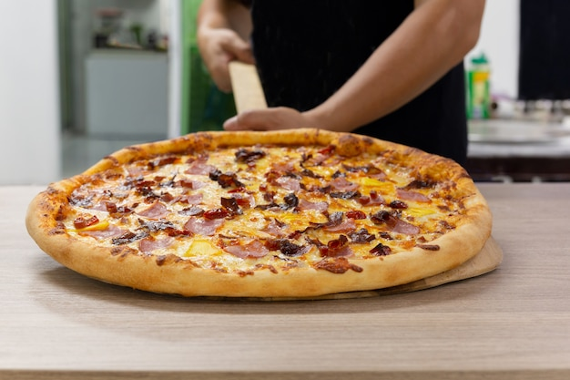 Chefs hand holding hawaiian pizza on wooden board. Premium Photo