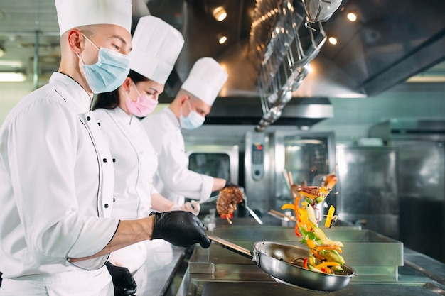 Chefs in protective masks and gloves prepare food in the kitchen of a restaurant or hotel. Premium Photo