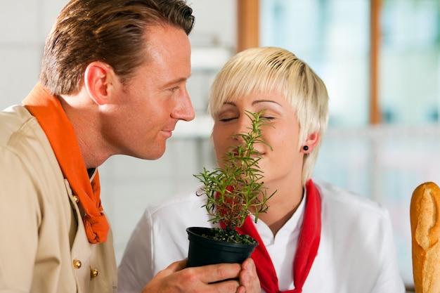 Chefs in a restaurant or hotel kitchen cooking Premium Photo