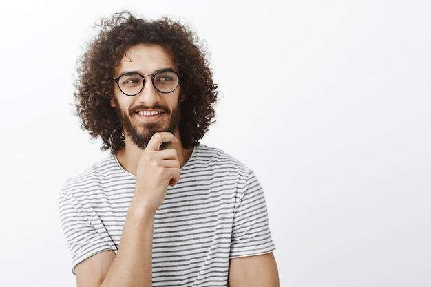 Проверь это. заинтригованный привлекательный кокетливый парень в игривом романтическом настроении, держащий руку на бороде, смотрящий вправо и улыбающийся с довольным любопытным выражением лица Бесплатные Фотографии