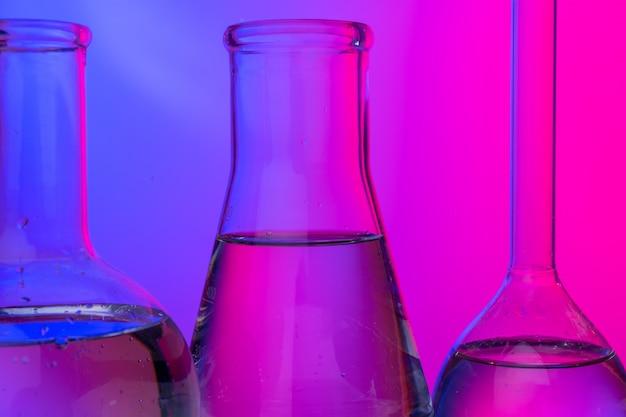 Chemical glassware close up on neon pink-purple Premium Photo