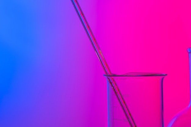 Chemical glassware close up on neon pink-purple Premium Photo