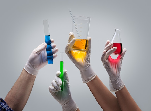 Руки химика, держа лабораторную посуду с жидкостями Premium Фотографии