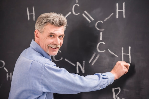 Chemistry writes on the blackboard formula in university. Premium Photo