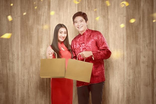 Азиатская китайская пара в платье cheongsam держит сумки Premium Фотографии