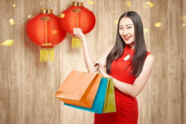 Азиатская китаянка в платье cheongsam держит сумки Premium Фотографии