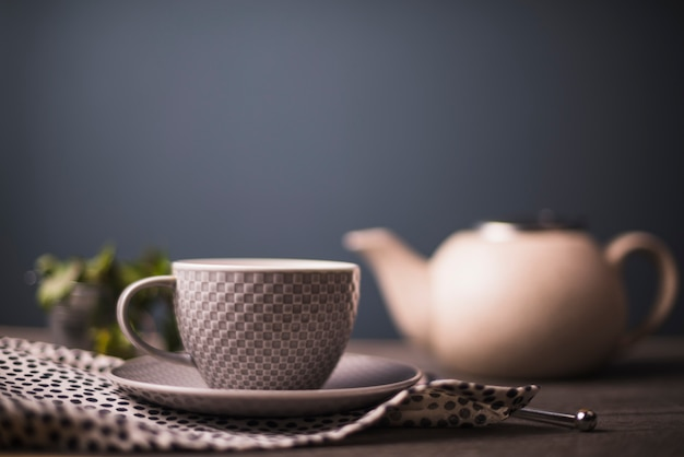 Chequered pattern tea cup on polka dotted textile on table Free Photo