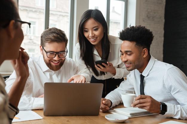 Cherful позитивные молодые коллеги, используя портативный компьютер. Бесплатные Фотографии