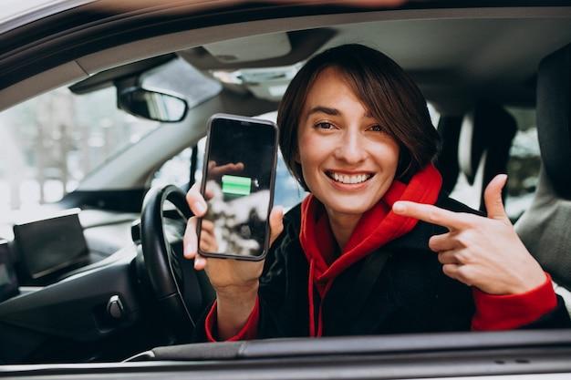 女性は彼女の車を充電し、彼女の電話でchergerを見て 無料写真
