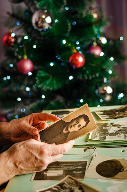 Черкассы / украина - 12 декабря 2019 г .: женские руки держат фотографию своей матери на фоне елки Premium Фотографии