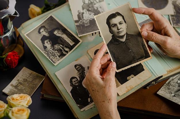 Черкассы / украина-12 декабря 2019 года: женские руки холдинг и старые фотографии ее матери. старинный фотоальбом с фотографиями. концепция ценностей семьи и жизни. Premium Фотографии