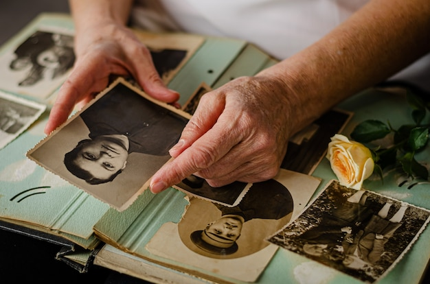 Черкассы / украина - 12 декабря 2019 г .: женские руки держатся за старые фото ее матери Premium Фотографии