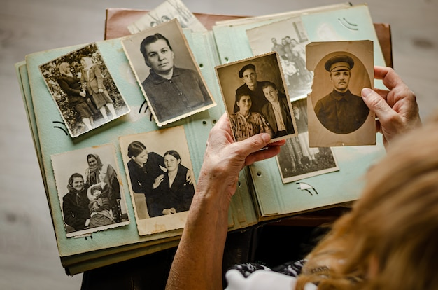 Черкассы / украина - 12 декабря 2019 года: женские руки держат и старые фотографии ее родственников. старинный фотоальбом с фотографиями. концепция ценностей семьи и жизни. Premium Фотографии