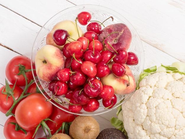 いくつかの野菜とチェリーと桃のカップ Premium写真