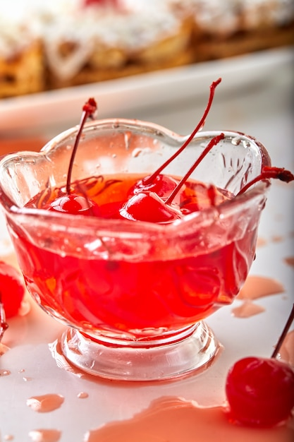 Cherries in sugar with sprigs in a cherry syrup in a transparent bowl Premium Photo